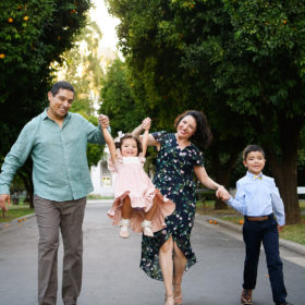 Mom and dad hold daughter's hand and lift her as they walk through orange trees in Sacramento Capitol