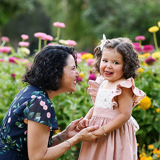 Toddler girl sticking her tongue out at the camera while mom looks at her and holds her hands by wildflowers in Sacramento Capitol