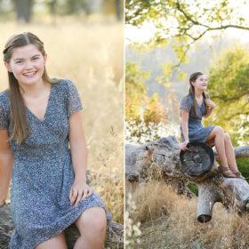 High school senior girl sitting on fallen log in dry grass and framed by tree branch Folsom