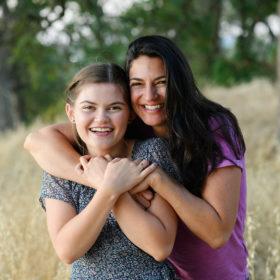 High school senior girl and mom hugging in dry grass field Folsom