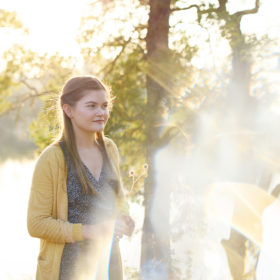High school senior girl standing next to tree in sunlight with lens flare Folsom