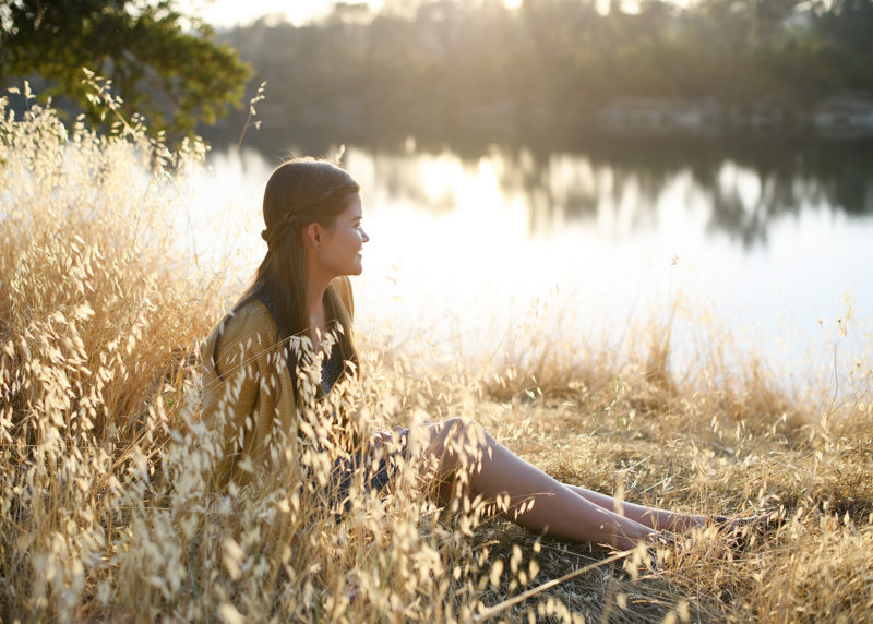 Teen girl sitting on dry grass by lake's reflection in natural sunlight in Folsom