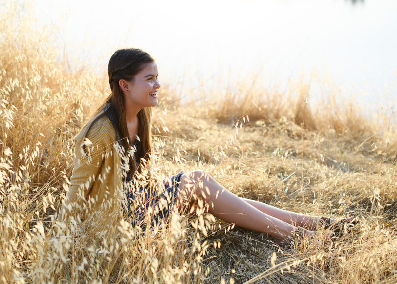 Teen girl sitting and smiling on dry grass by lake's reflection in natural sunlight in Folsom