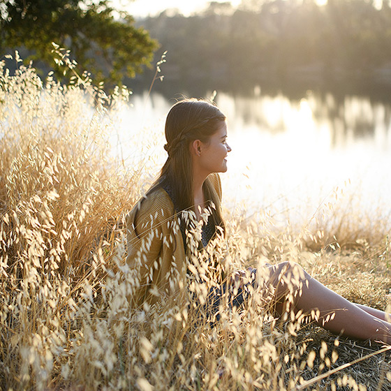 Teen girl sitting on golden dry grass by Folsom Lake reflection