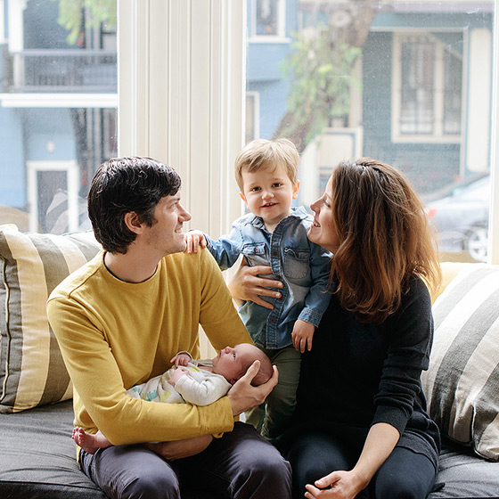 Dad holding newborn as mom holds big brother by bay windows in San Francisco