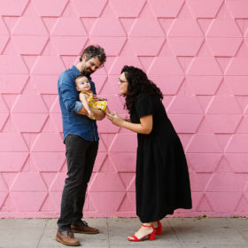 Mom looks at baby daughter as dad holds her against a pink tiled wall in midtown Sacramento