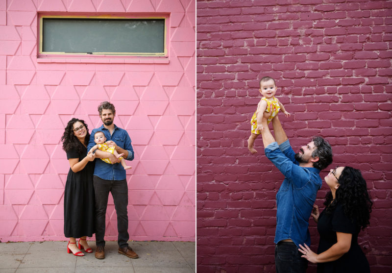 Mom and dad hold baby daughter in front of colorful pink and purple brick walls in midtown Sacramento