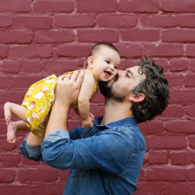 Dad kissing baby daughter on cheek as she smiles against purple brick background in Sacramento