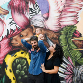 Dad carrying baby daughter on shoulders as mom watches in front of Sacramento mural