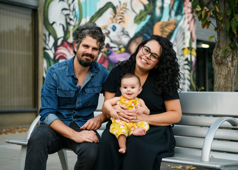 Mom holds baby daughter while sitting on bench and mural as background in Sacramento