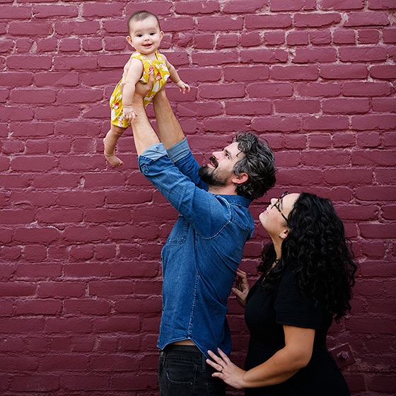 Dad lifting up baby girl while mom watches with purple brick background in Sacramento