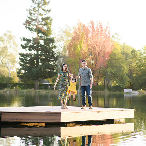Mom and dad swing toddler daughter on dock by lake in Bywater Hollow Lavender Farm